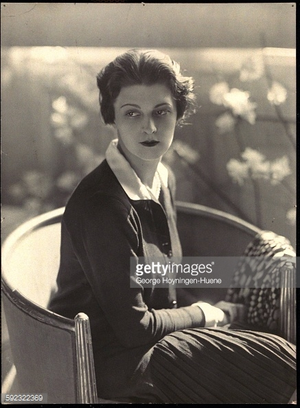 Mrs. Michael Arlen (formerly Countess Atlanta Mercati) wearing dark-colored knit dress with long sleeves, pleated hem, and contrasting collar; sitting in a chair *** Local Caption *** Atlanta Arlen;